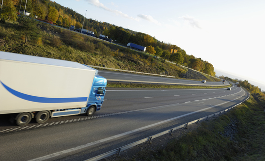 Semi truck driving down freeway towards trade show