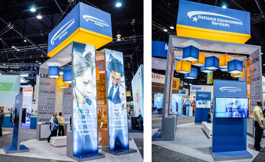Backlit Island Trade Show Display with Monitor Kiosks and Large Hanging Sign