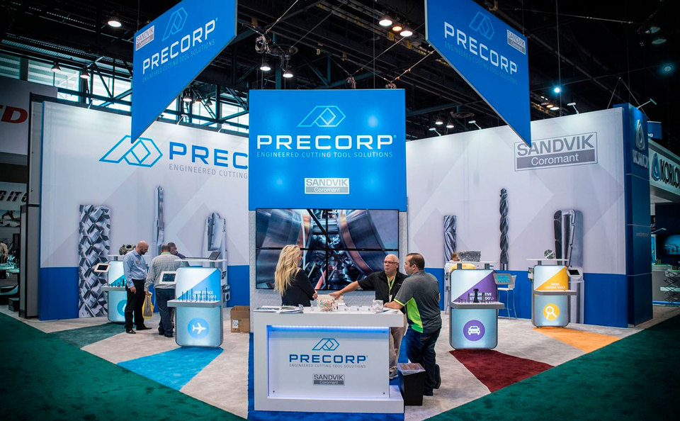 Precorp Island Trade Show Display with Kiosks, Bold Graphics and Backlit Reception Counter
